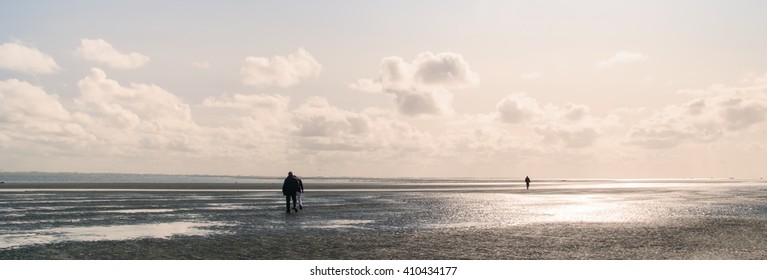 Three people on the deserted east side of the Dutch island Schiermonnikoog. The tide comes in.