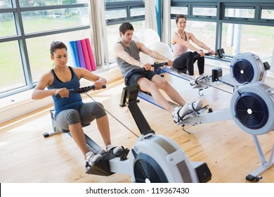 Three people on rowing machines in fitness studio