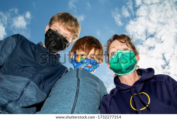 Three people outside wearing COVID-19 face masks with the blue sky in the background.