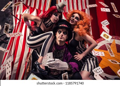 Three people performing on stage freak show, showing magic tricks with cards on dark circus scene