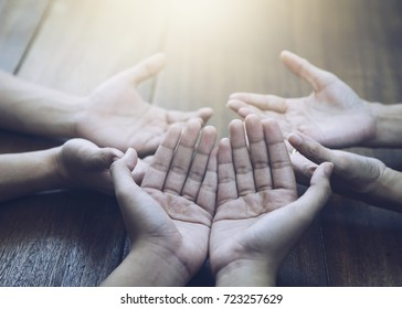 Three people pray and praising God together over wooden table with the light from above, copy space.