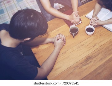 Three people pray together on wooden table in living room, family worship, Christian background