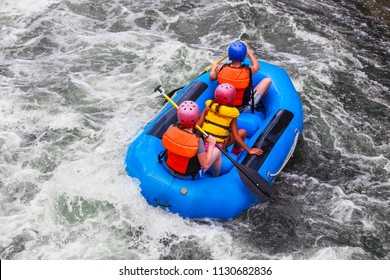 Three people in a raft in white water rapids