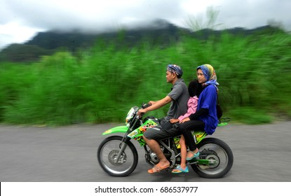 Three people are riding motorbikes. Awareness to use safety helmets for motorcycle riders, is still very minimal among motorists in Indonesia, especially in Yogyakarta on December 24, 2012.