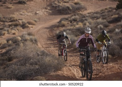 Three people are riding mountain bikes uphill in a desert landscape. Horizontal shot.