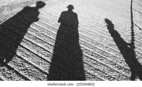 Three people shadows on striped cement surface. Two person standing and male old one walking leaning on the railing. Abstract life relations concept background. Black and white photo.