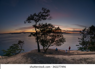 Three People sit and watch the sunset on Stuart Island, one of the San Juan Islands in Washington