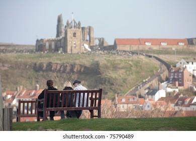 Three people sitting on a bench and looking at an abbey in Whitby