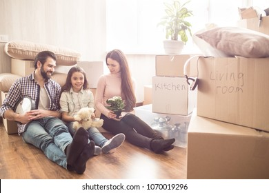 Three people are sitting together on the floor. They are surrounded with boxes full of stuff. Father is holding big clock in hands, mother is holding a beautiful plant. Their girl is holding a bear