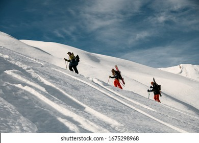 Three people with ski equipment and sticks climbs snowy mountain. Blue sky and snow-capped mountain in background.