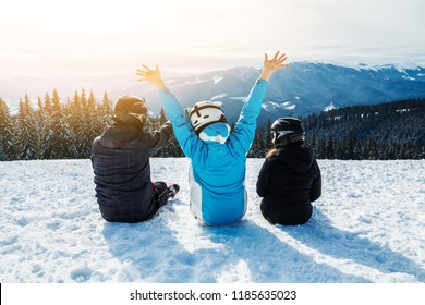 Three people in ski suits are sitting on the snow at the top of the mountain and looking into the distance. Family of skiers resting on the top of the mountain. back view