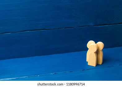Three people stand together and talk. Three wooden figures of people conduct a conversation on a blue background. Communication, meeting place. Place for text. Minimalism