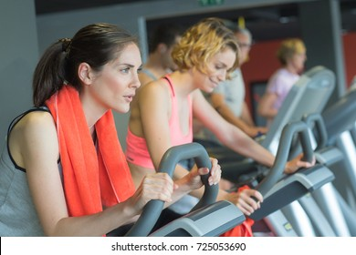 three people stepping on step machine in gym