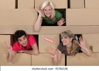 Three people surrounded by boxes
