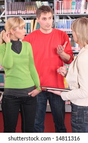 three people talking in the library