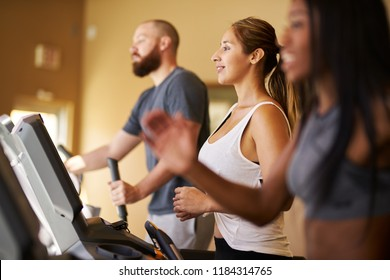 three people using treadmills in gym together