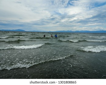 Three people wading wading into the cool ocean waters of the Pacific Northwest at low tide.