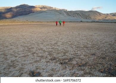 Three people walk across the desert playa towards sand dunes.