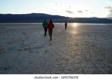 Three people walk across a desert playa towards the sunset.