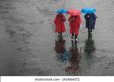 Three people walking in the rain with umbrella and raincoat.