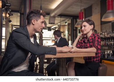 three people, young adult couple, holding hands, coffee shop indoors, table