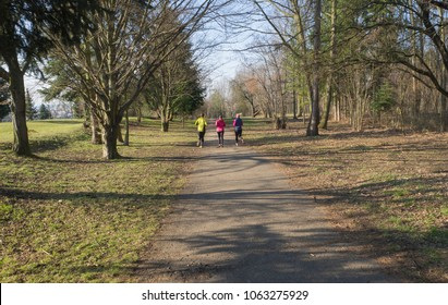 three people , young women and men running or jogging on publick park road in Prague Hostivar, early spring sunny day, tree and blue sky background