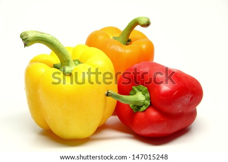Three Peppers A whole yellow, orange and red pepper.  The background of the image is white.