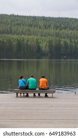 Three person backs with colorful t-shirts in front of the lake. Vertical landscape with three unknown persons.