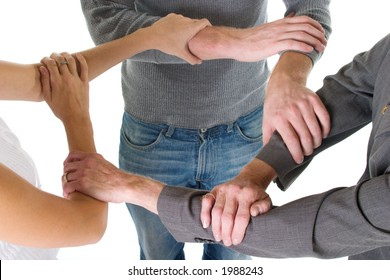 Three person business team with hands and arms linked in unity and support.