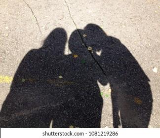 three person shadows discuss some secret