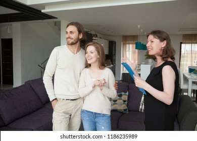 Three person standing in living room. Realestate agent, realtor showing property house for sale or tenant to young satisfied married couple. New home, moving and real estate loan and mortgage concept