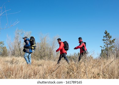 Three persons in the autumn sport hiking, walking and backpacking