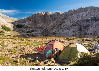 Three persons, two men and a woman, making camping tents at a remote campsite in the wilderness of the mountains, after a hike, in Bariloche, Neuquén, Patagonia Argentina