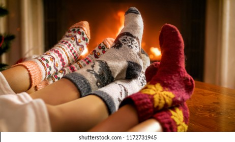 Three persons in woolen knitted socks warming by the burning fireplace