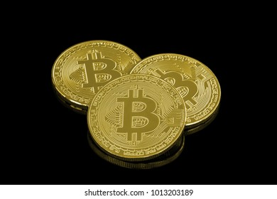 Three physical golden Bitcoin coins isolated on a reflective, black surface. Conceptual image to visualize cryptocurrency.