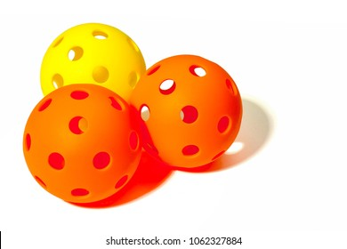 Three Pickleballs - 2 Orange and 1 Yellow together on a white background.