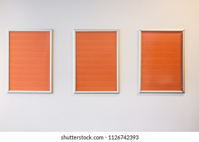 Three picture frames with orange copy space hanging on white wall