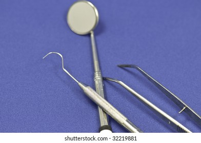Three piece dental instrument on a blue background. The focus is on the center of the front pick.