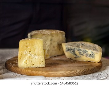 Three pieces of cheese. Ripe yellow cheese and blue cheese on a wooden board. Food, wine and romantic, cheese and delicatessen. Text area space