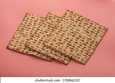 Three pieces of matzo bread (traditional unleavened bread usually prepared for Jewish Passover celebration). Pink background.