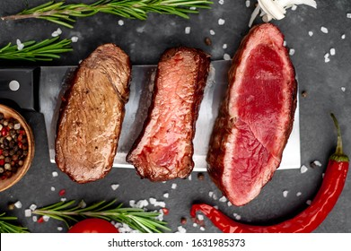Three pieces of meat grilled over a meat knife Three types of frying meat, rare, medium, well done, with spices   on stone background