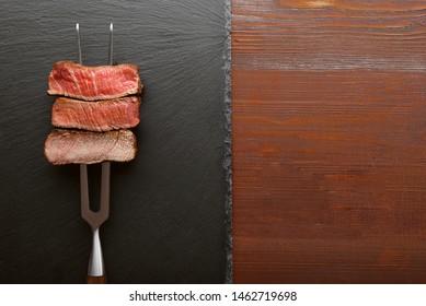 Drei Stück Fleisch auf einer Gabel für Fleisch. drei Fleischgeröstungen, selten, mittel, gut gemacht.