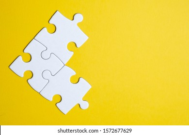 Three pieces of a puzzle united among themselves on a yellow background. Teamwork concept. Close up.
