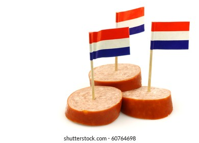 three pieces of smoked sausage with Dutch flag toothpicks on a white background