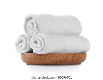 three pieces of white towels on wooden plate