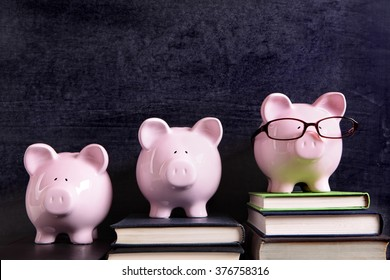 Three piggy banks in a row with blackboard background, college success concept