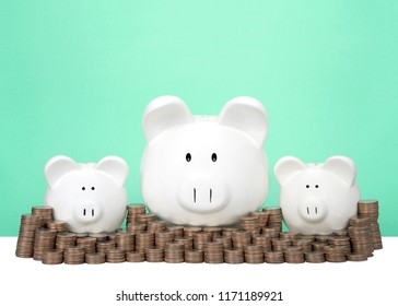 Three piggy banks in a row one large two small behind a wall of coins stacked in piles. Wall of savings. Dollar signs in their eyes. Light green background with copy space.