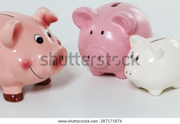 Three piggybanks on table closeup. Budgeting expenses and sharing savings concept. Making savings and effective investment concept. Future needs deposit