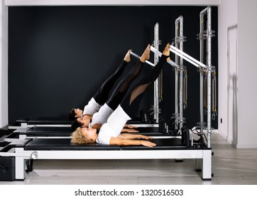 Three Pilates women in reformer tower exercise at gym