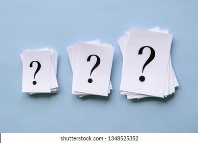 Three piles of question marks printed on white paper in different sizes arranged in a row on a blue background in a conceptual image